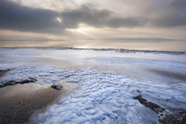 View of sandy beach against water and clouds in sky during daytime — Stock Photo