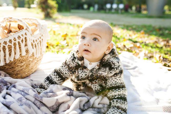 Портрет мальчика, сидящего на одеялах на открытом воздухе — стоковое фото