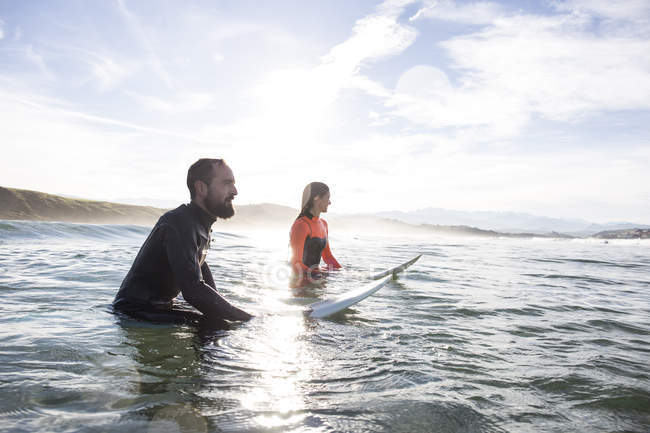 Couple of surfers in ocean waiting for wave — Stock Photo