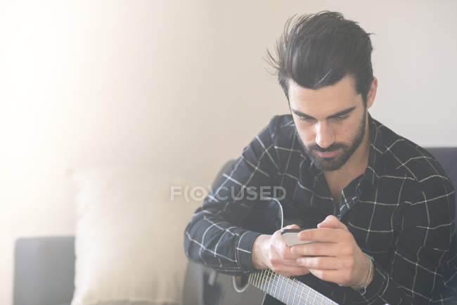 Man with smartphone and  guitar — Stock Photo