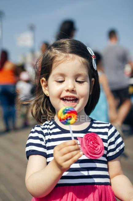 Нью-Йорк, Коні-Айленд, портрет щасливі маленька дівчинка тримає барвисті льодяник над доріжки у Сонячний літній день — стокове фото