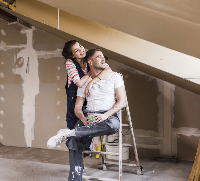 Portrait of young couple on ladder looking aside — Stock Photo