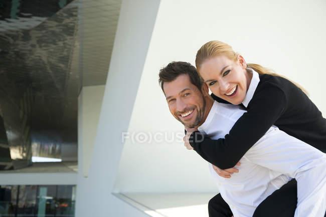 Портрет счастливого бизнесмена, несущего женщину на спине — стоковое фото