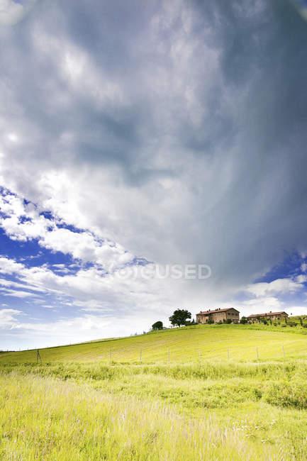 Blick auf grüne Wiese mit Stall unter Wolken — Stockfoto