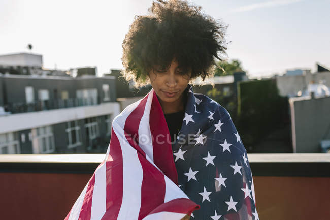 Portrait of young woman wrapped in American flag — Stock Photo