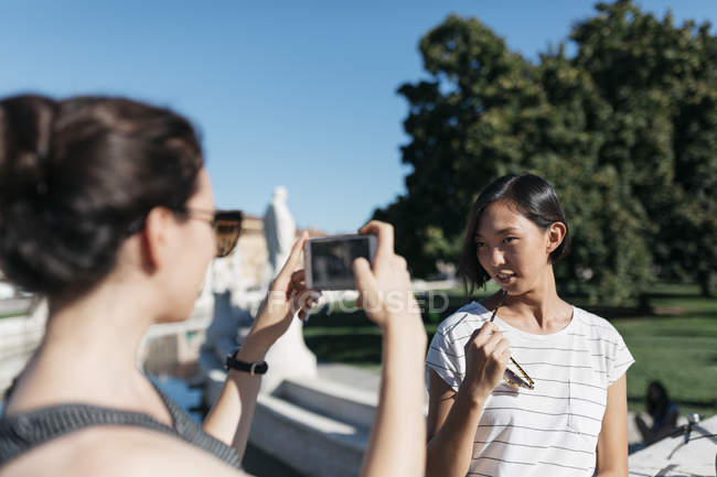 Young woman taking picture of friend with smartphone — Stock Photo