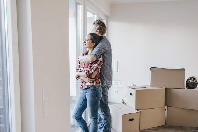 Happy couple standing at window of new home — Stock Photo