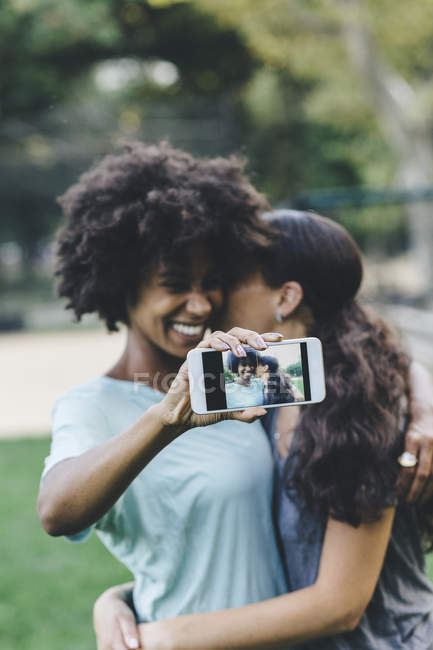 Two women taking selfie with smartphone in a park — Stock Photo