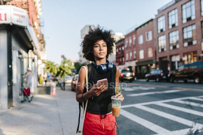 Portrait of young woman walking at street with smartphone — Stock Photo