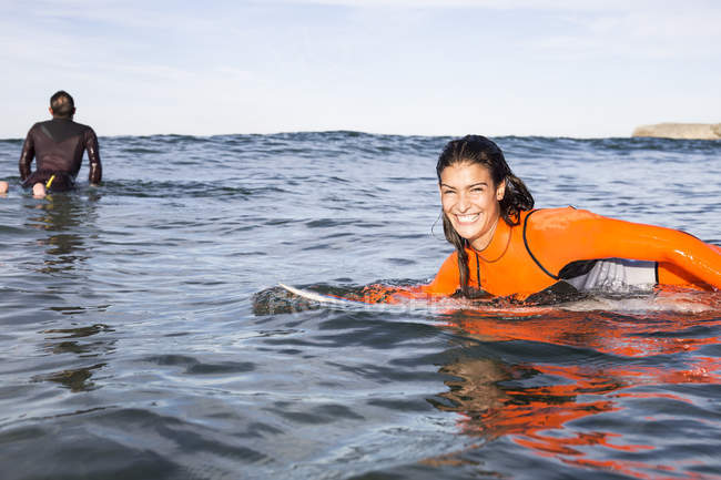 Woman lying on surfboard in sea smiling at camera, rear view of man on surfboard waiting for wave on background — Stock Photo