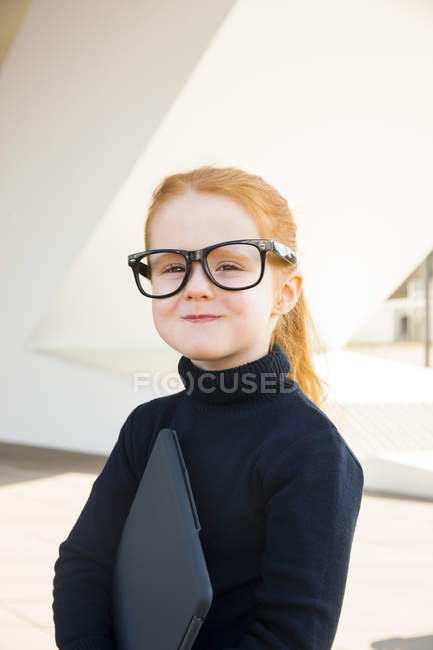 Girl wearing oversized glasses holding laptop — Stock Photo