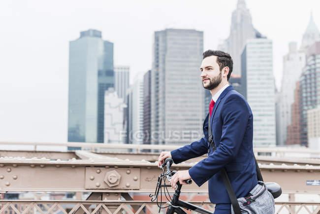 États-Unis, New York, Brooklyn bridge, Vue latérale d'un jeune homme d'affaires à vélo — Photo de stock