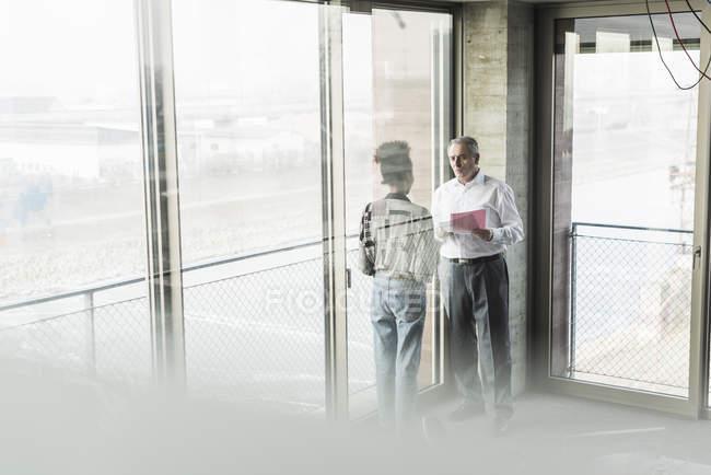 Старший бизнесмен, обсуждая документы с молодой сотрудник в офисе — стоковое фото