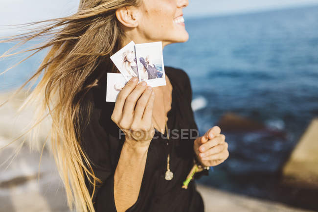 Jovem mostrando fotos instantâneas de si mesma à beira-mar — Fotografia de Stock