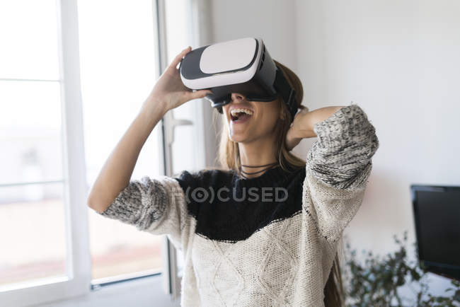 Woman wearing VR glasses at home — Stock Photo