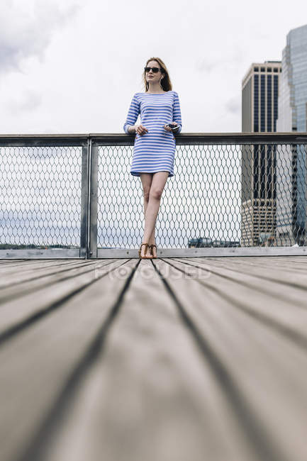 Молодая женщина, стоящая на Манхэттене за перилами, держа смартфон — стоковое фото