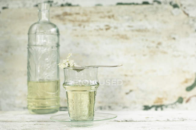 Glass and glass bottle of elderflower sirup — Stock Photo