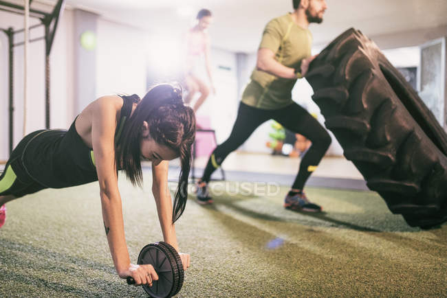 Group of sporty caucasian young people training in gym — Stock Photo