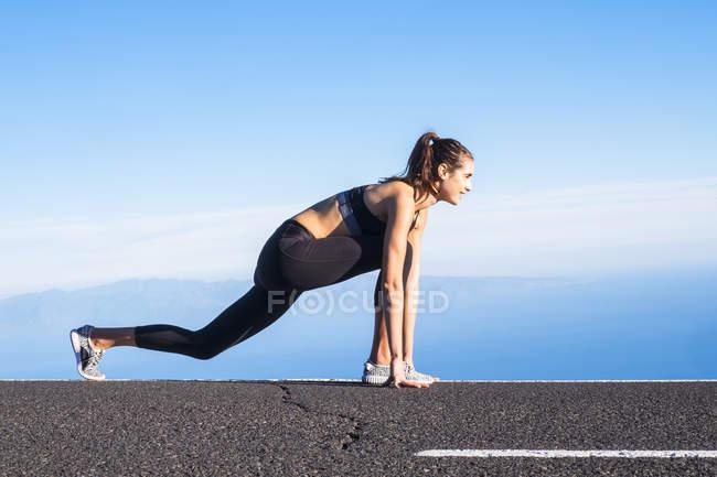 Боковой вид молодой привлекательной кавказской женщины, занимающейся спортом — стоковое фото