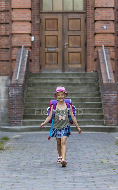 Menina a sorrir com saco de escola, andar na frente de escola — Fotografia de Stock