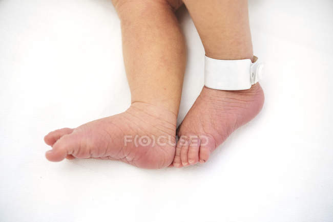 Close-up of Newborn baby feet with label in hospital — Stock Photo