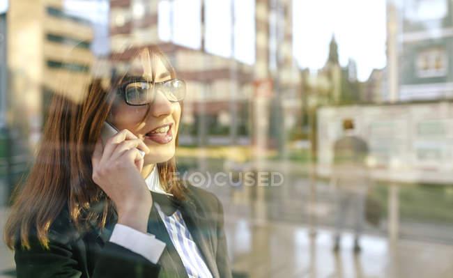 Деловая женщина разговаривает по телефону перед стеклом — стоковое фото