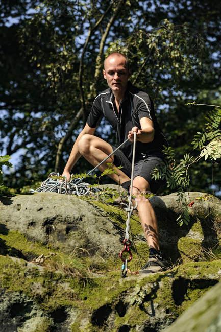Confiant grimpeur accroupi sur un rocher dans la nature — Photo de stock