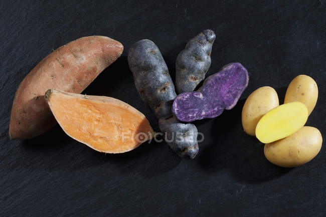 Top view of three sorts of whole and cut potatoes — Stock Photo