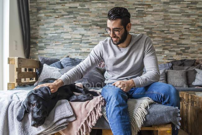 Ritratto ritagliato di uomo coccole cane nero — Foto stock