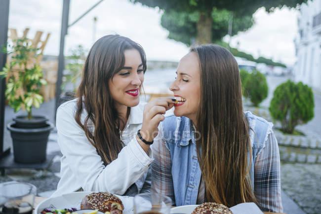 Portrait de deux jeunes femmes partageant une croustille dans un restaurant de trottoir — Photo de stock