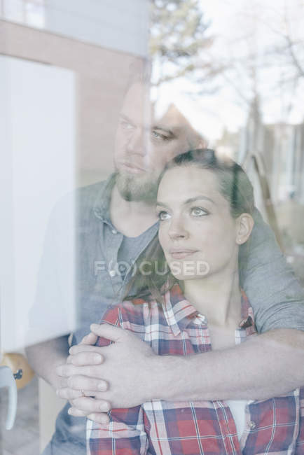 Couple standing at window of new home — Stock Photo