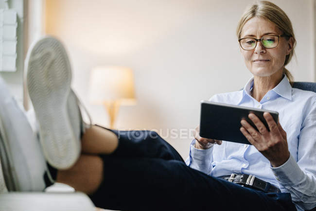 Businesswoman sitting and using tablet — Stock Photo