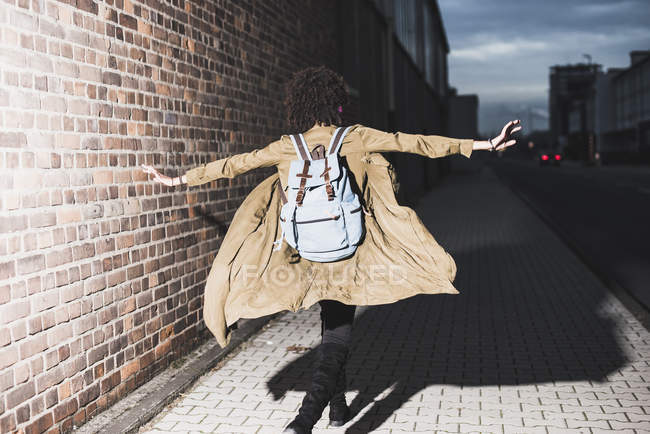 Молодая женщина с рюкзаком бежит с протянутыми руками — стоковое фото