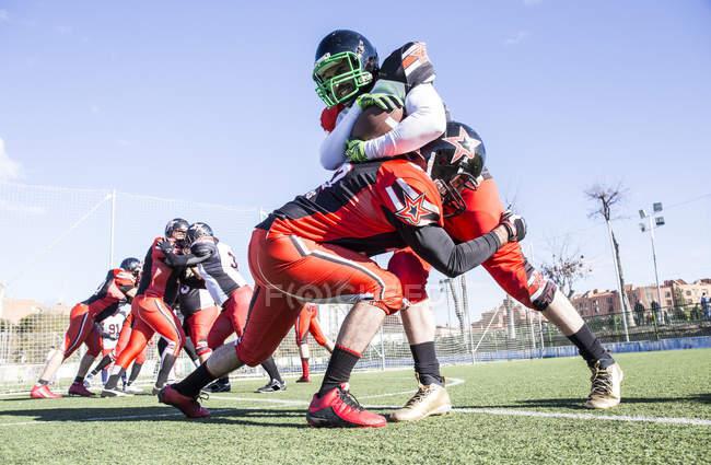 Jogador de futebol americano sendo abordado pelo jogador adversário durante uma partida — Fotografia de Stock