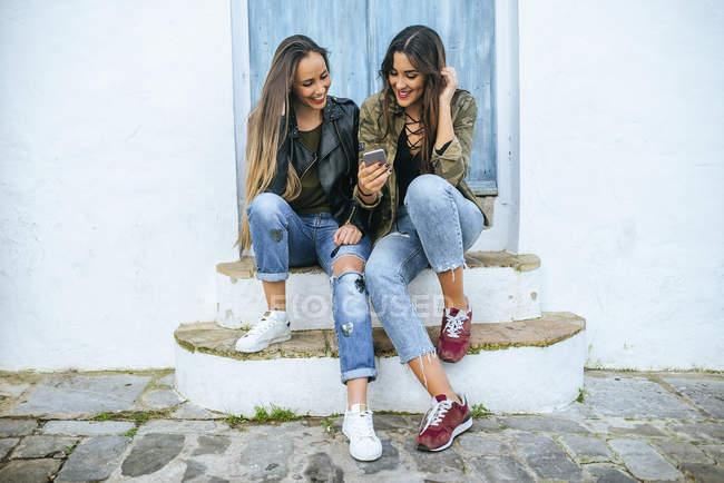 Duas jovens mulheres sentadas em uma porta azul olhando para um telefone celular — Fotografia de Stock