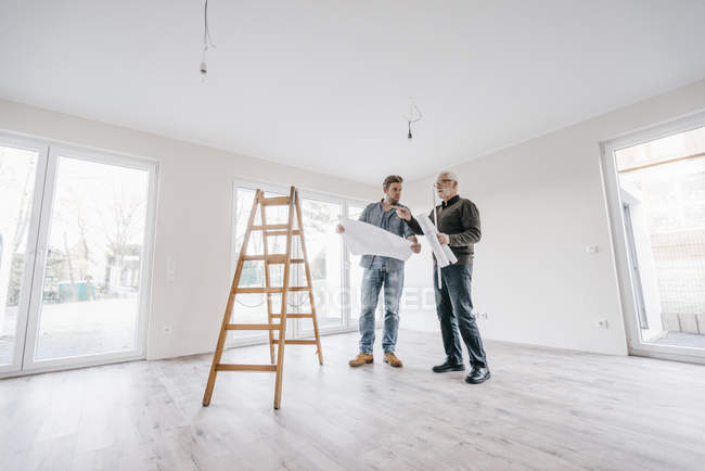 Architect checking construction plan with owner of the new home — Stock Photo