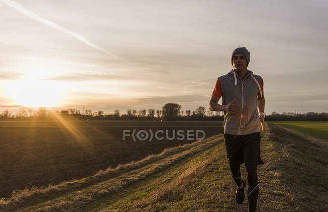 Portrait of young man running in field at sunset — Stock Photo