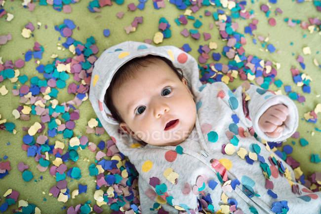Menina atônito, rodeada de confetes coloridos — Fotografia de Stock