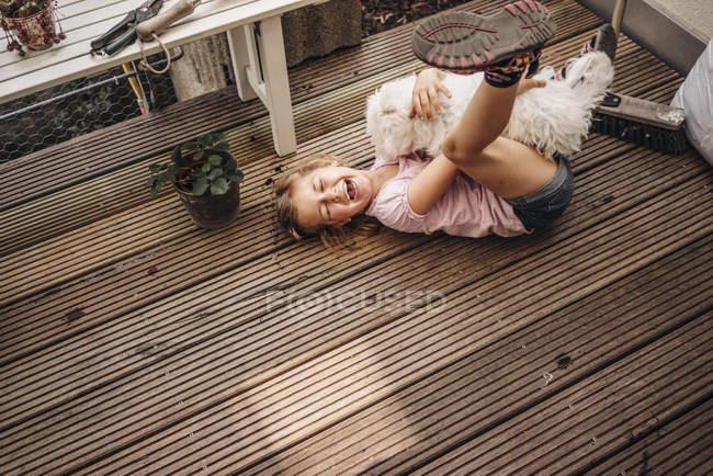 Menina feliz brincando com o cão no terraço de madeira — Fotografia de Stock
