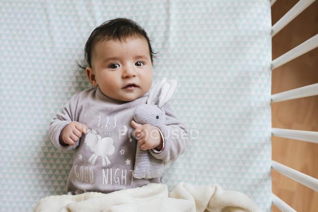 Cute baby girl lying in crib holding stuffed rabbit — Stock Photo