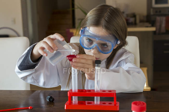 Girl wearing work coat and safety glasses using chemistry set at home — Stock Photo