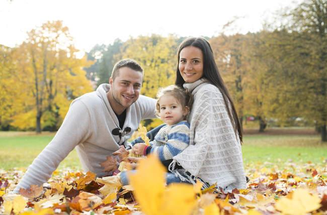 Familia feliz sentado en hojas de otoño - foto de stock