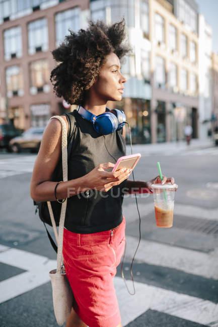 Retrato de jovem caminhando com smartphone e bebida — Fotografia de Stock