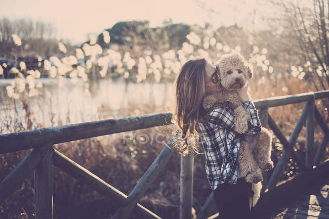 Woman standing on bridge and holding dog — Stock Photo
