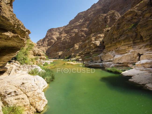 Vista de Omã, Wadi Tiwi, da lagoa, rodeada por rochas — Fotografia de Stock