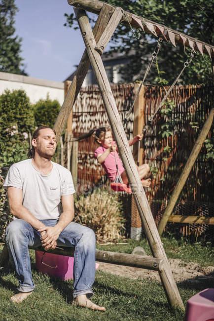 Вичерпані батька з дочкою на гойдалки в саду — стокове фото