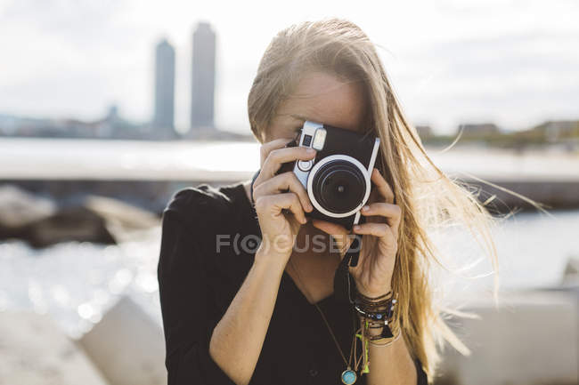 Young woman taking picture with old-fashioned camera at seafront — Stock Photo