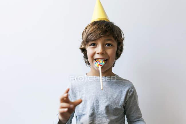 Портрет мальчика в шляпе с леденцом во рту — стоковое фото