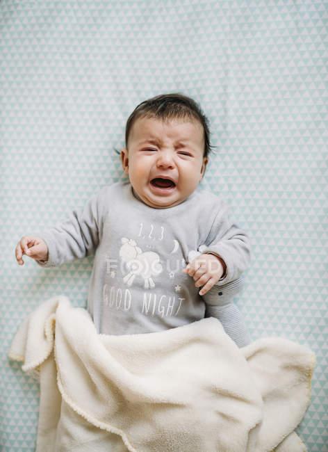 Menina chorando na cama com o coelho de peluche — Fotografia de Stock
