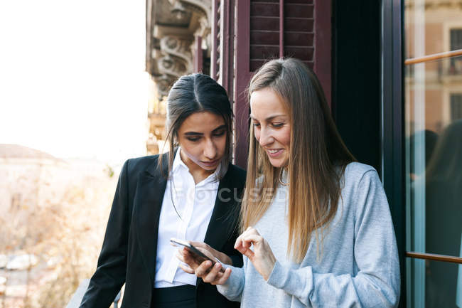 Portrait of two young women using smartphone on balcony — Stock Photo